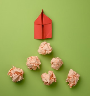 Red paper airplane and crumpled paper balls on a green background, top view. the concept of finding innovative ideas, the right solutions. elimination of mistakes and a leap forward for the leader