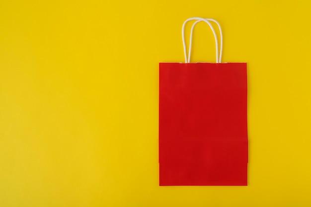 黄色の背景に赤い紙袋。ショッピングバッグ。スペースをコピーします。モックアップ。