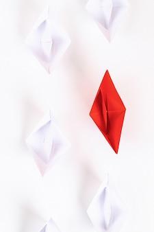 Красный бумажный кораблик среди других белых. лидерство, белая ворона, индивидуальность. оригами. вид сверху, плоская планировка