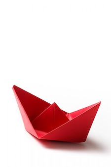 A red paper boat on a bright blue surface. copy space