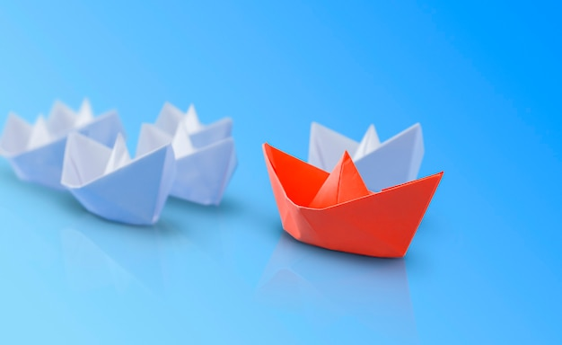 Red paper boat in front of the white ones. blue background