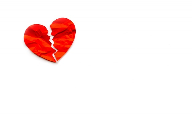 Red paper broken heart on white background