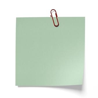 分離された緑の紙の上の赤いペーパークリップ