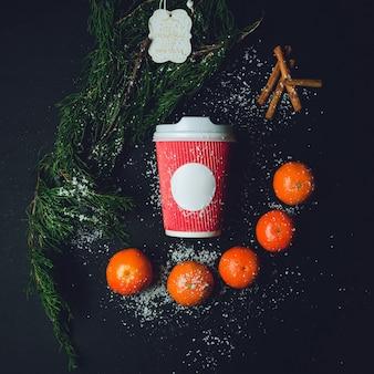 Красный бумажный стакан лежит между веткой ели, оранжевыми мандаринами и палочками корицы