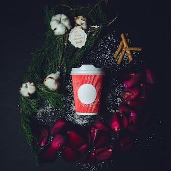 Красный бумажный стаканчик лежит между еловыми ветвями, цветками ваты и лепестками роз