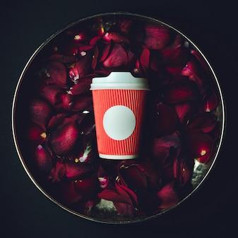 Красный бумажный стаканчик лежит в миске с лепестками роз