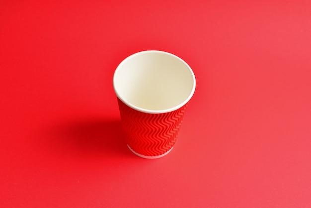 赤い背景の上の赤い紙コップ。スペースをコピーします。