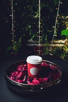Красный бумажный стаканчик в миске с лепестками роз