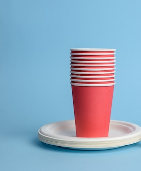Red paper cup, white plates on a blue surface