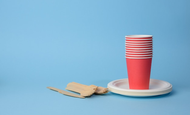 Red paper cup, white plates and wooden forks and knives on a blue surface. plastic rejection concept, zero waste , copy space