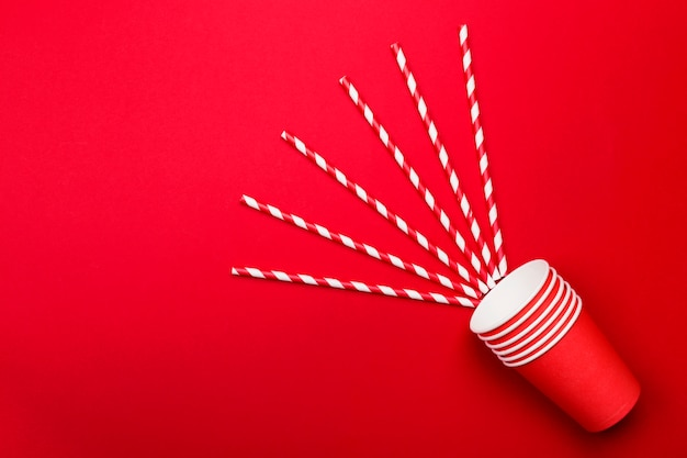 Red paper cups and red-white straw on red. top view, copy space
