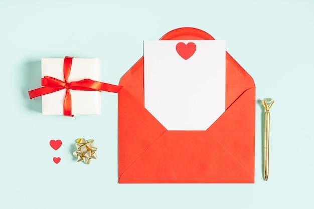 空白の白いメモのモックアップと赤い紙の封筒。バレンタインギフトと青い作業テーブルの背景のフラットレイ