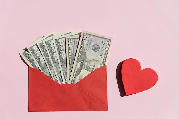 Красный бумажный конверт с долларовыми купюрами и красным сердцем на розовом фоне