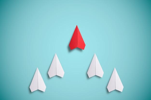 Красное бумажное летание перед белой бумагой. концепция лидерства.