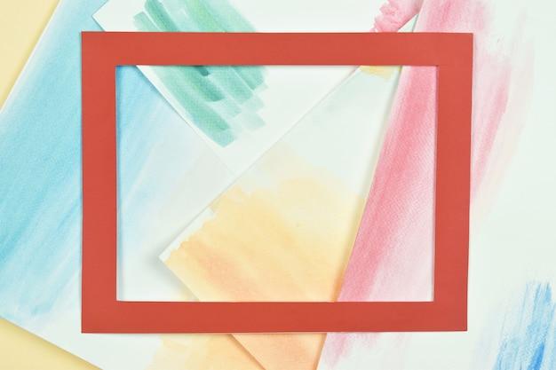 다채로운 수채화 손에 빨간 종이 프레임 흰 종이에 수채화 스트로크를 그린