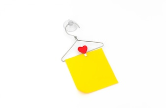 Red paper heart hanging on white background .