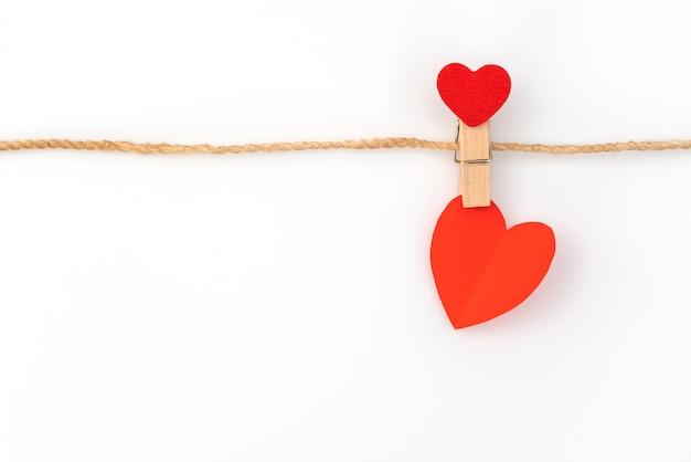 Красная бумага сердце висит на белом фоне.