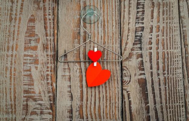 Красная бумага сердце висит на фоне дерева.