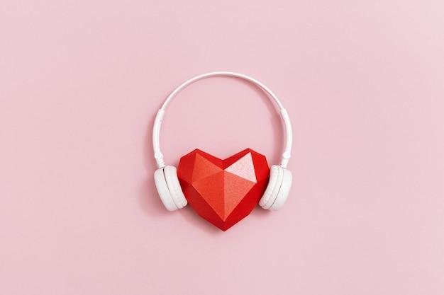 Красное бумажное сердце в белых наушниках концепция музыкальных фестивалей, радиостанций, любителей музыки