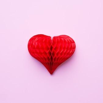 Красное бумажное сердце на розовом. вид сверху