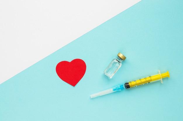 액체 건강 및 예방 접종 개념 의료 주사가 있는 빨간 종이 심장 주사기 및 유리병