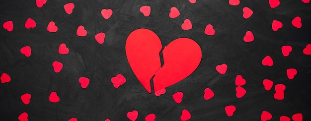 Red paper heart torn to pieces on black background concept of sadness, unhappy love, broken heart. copy space