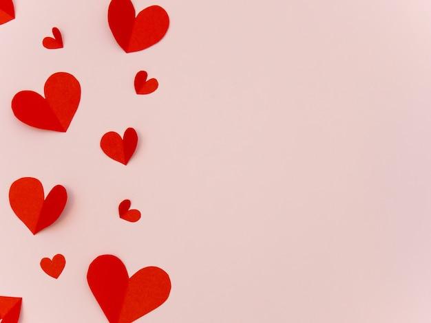 テキストのコピースペースとピンクの背景に赤い紙のハートバレンタインデーカード。