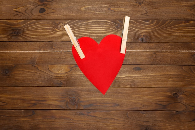 Red paper heart valentines hanging on the rope on the clothespin