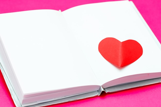 Red paper heart over white opened book on pink surface