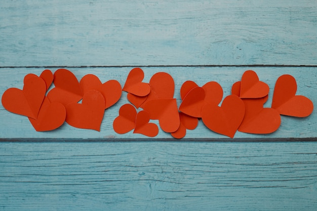 Red paper hearts on a blue wooden background