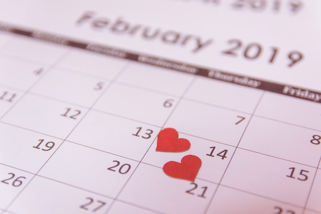 Red paper hearts on calendar page