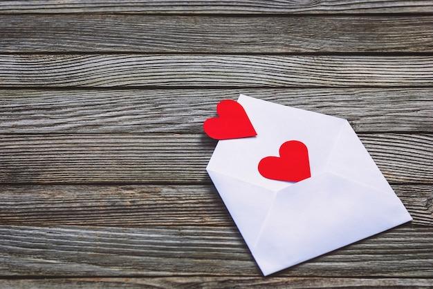 Красные бумажные сердечки в конверте на деревянных фоне