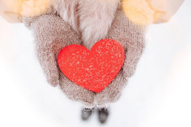 눈 덮인 겨울 공원에서 외부 모직 장갑을 끼고 여자의 손에 빨간 종이 마음. 로맨틱 한 여자는 사랑의 상징으로 발렌타인을 기념합니다. 2 월 14 일 서명.