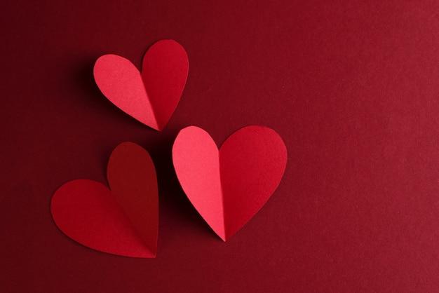 Красная бумага сердечки на темно-красном. день святого валентина монохромная концепция карты