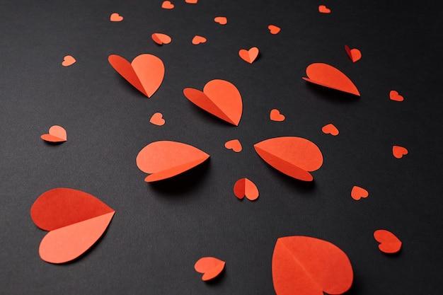 Красные бумажные сердечки на черном фоне