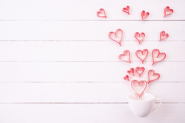 Red paper hearts splash out from white coffee cup on wooden background.