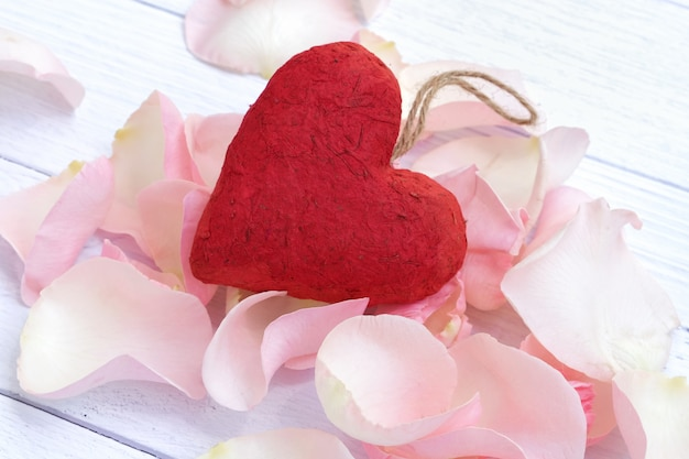 A red paper mache heart on a bed of pink rose petals