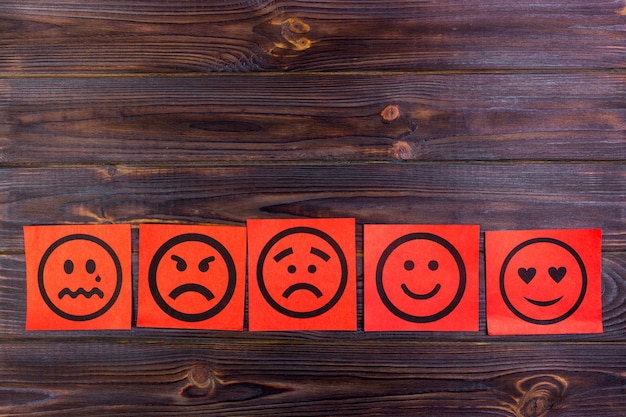 Red paper notes with happy, joy, anger, laughter and sad faces on blackboard. vignette