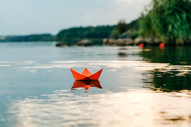 Red paper origami boat floats on the surface of the water and reflects itself