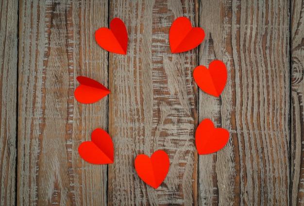 나무 바탕에 빨간 종이 접기 심장.