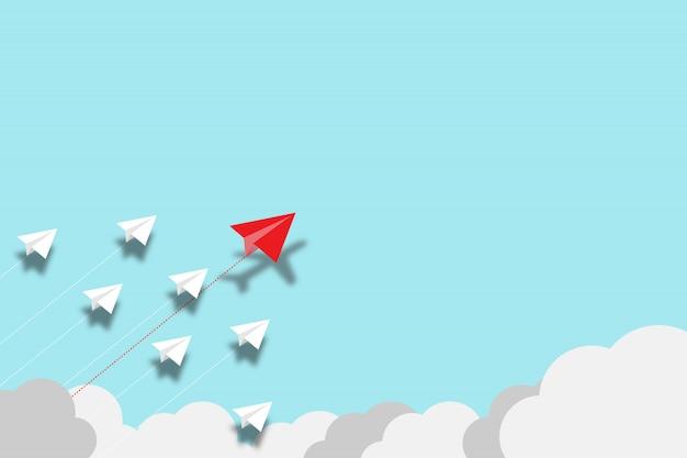 赤い紙飛行機が青い背景に白い紙飛行機で混乱を飛んでいます。イノベーションを発見し、ビジネスの創造性を高める新しいアイデア。