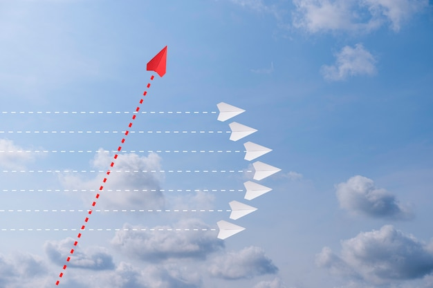 Red paper plane out of line with white paper to change disrupt and finding new normal way on sky background. lift and business creativity new idea to discovery innovation technology.