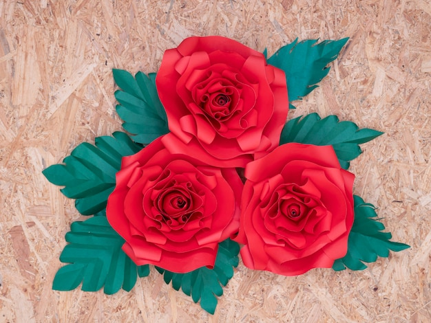 Red paper roses with green leaves