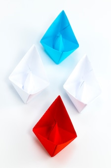 Red paper ship and blue paper ship leading among white paper ships