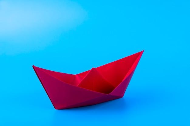 Красный бумажный корабль в новом направлении на синем фоне, новая нормальная концепция, копия пространства