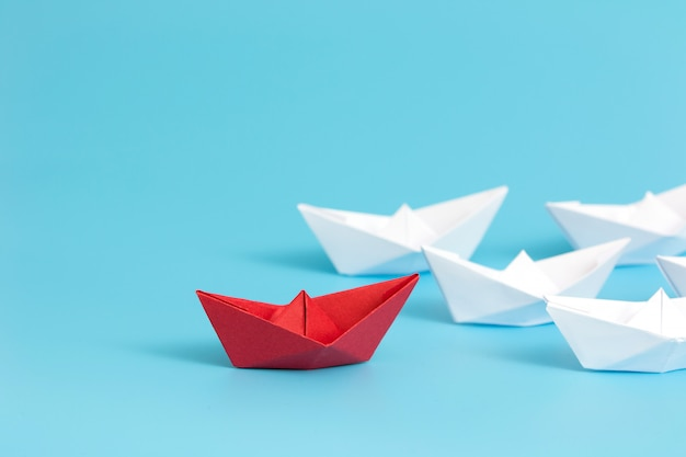 Red paper ship leading among white on blue background with copy space.