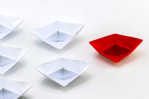 Red paper ship leading among white paper ships