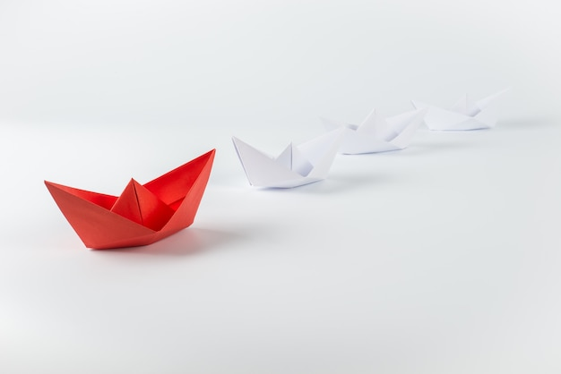 Red paper ship leading among white