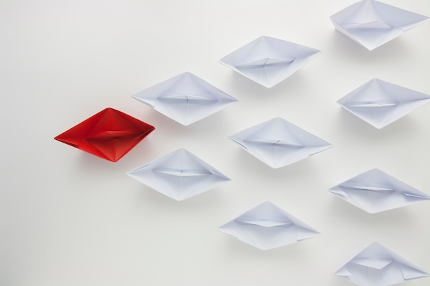 Red paper ship leading white ones, leadership concept