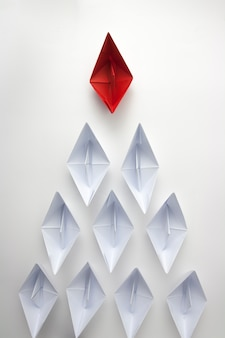 Red paper ship leading white ones